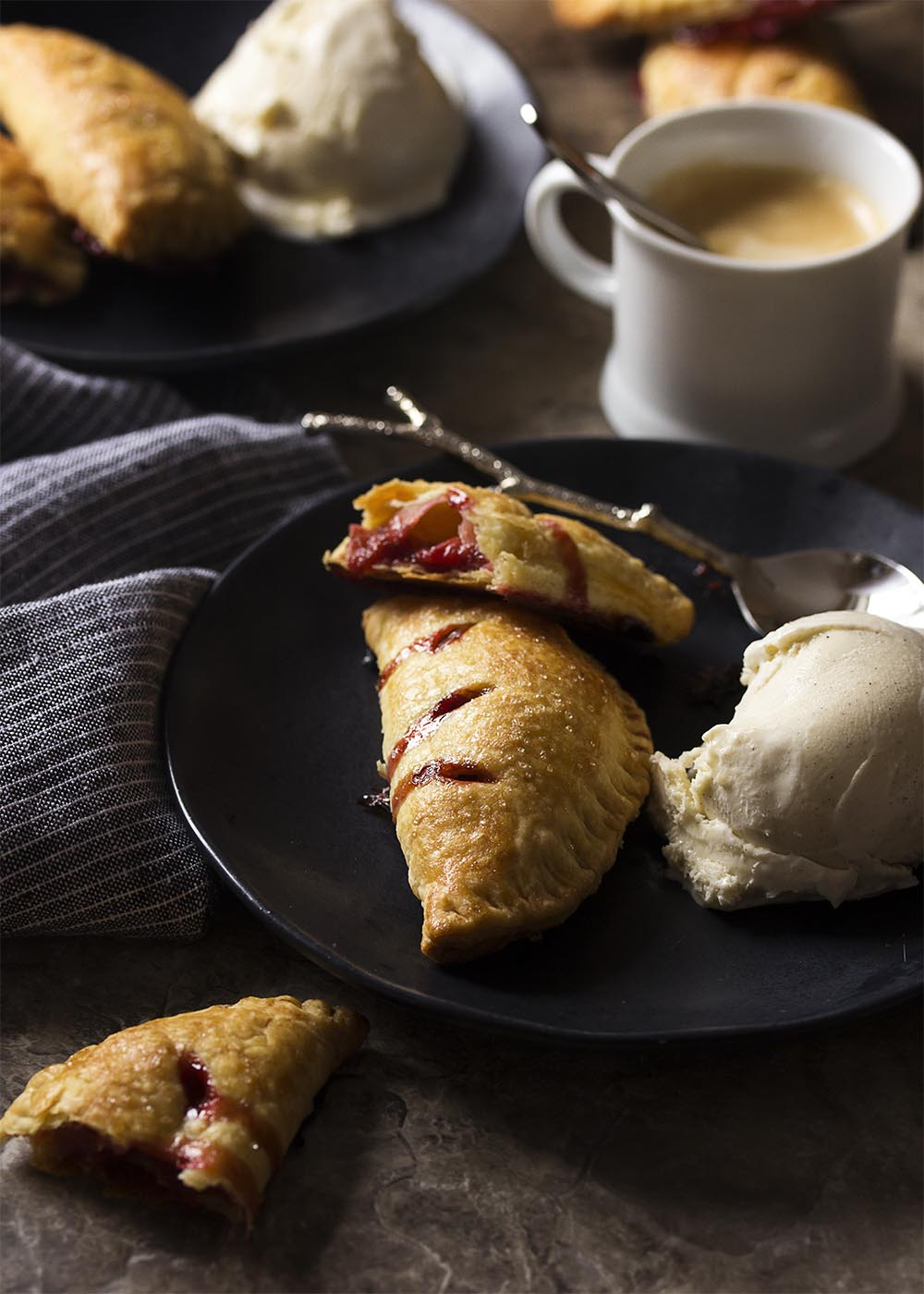 Strawberry rhubarb hand pies on a plate with vanilla ice cream and one pie broken up to show the filling.