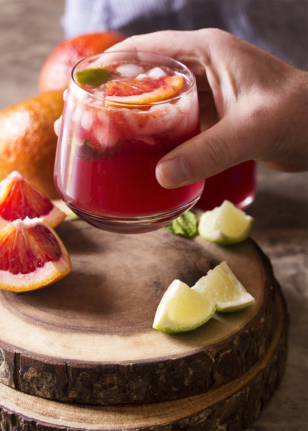 A hand lifting a glass of blood orange Moscow mule with orange and lime slices scattered about.