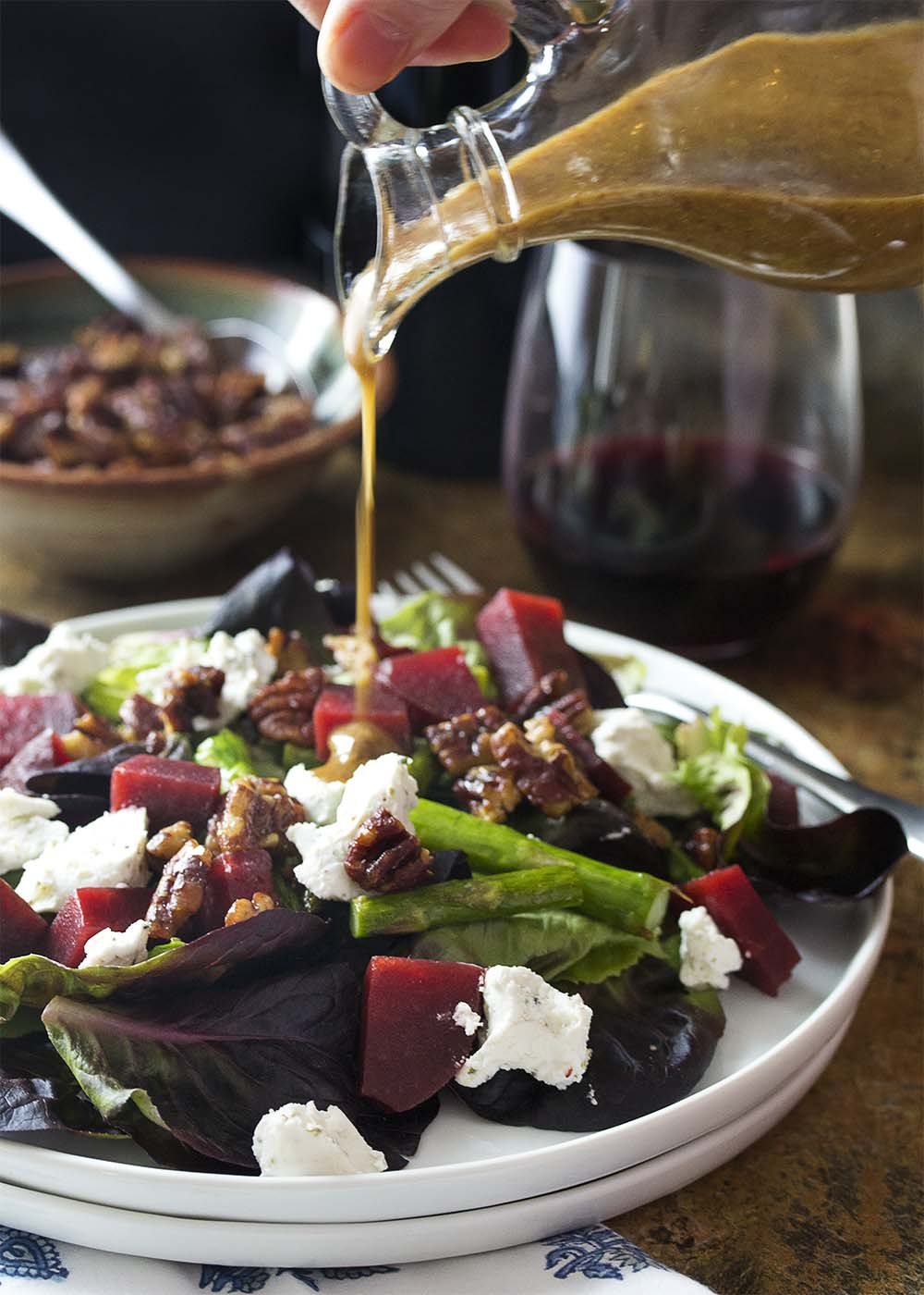 Pouring mustard balsamic dressing over a plate of French country salad topped with goat cheese and pecans.