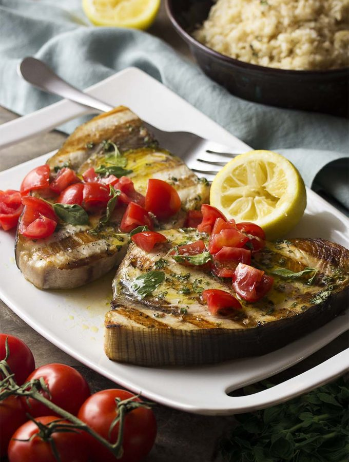 Sicilian swordfish is an easy dinner recipe perfect for a summer's evening. Just fire up the grill to cook your summer squash and then the swordfish steaks, top it all with a tangy lemon and olive oil oregano sauce and some diced tomatoes, and you have a meal!