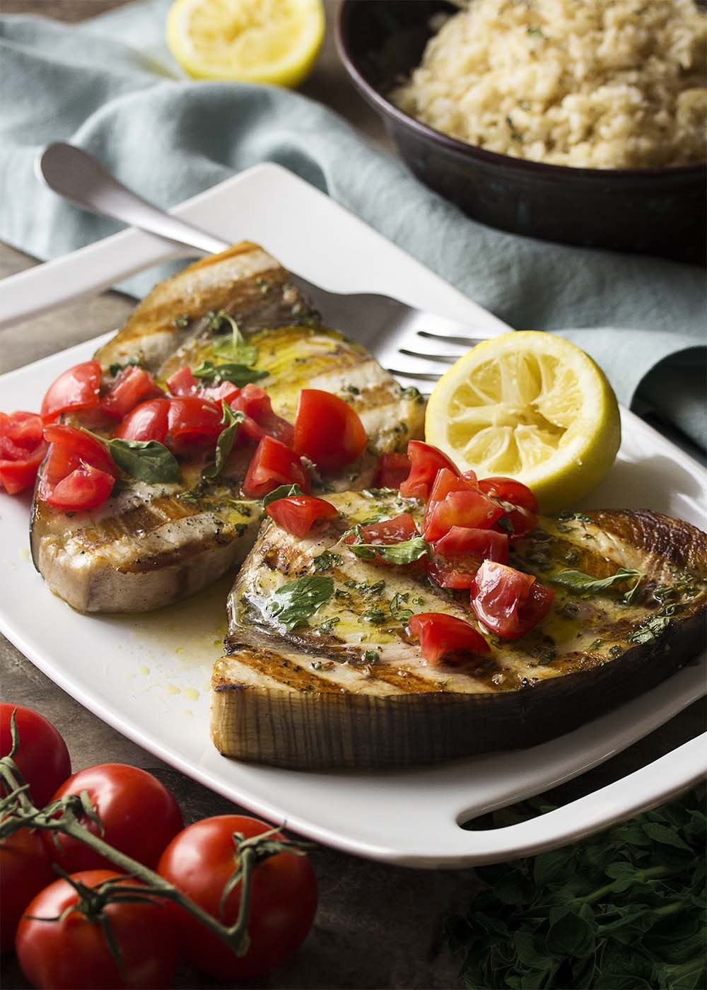 Grilled Sicilian swordfish on a platter with chopped tomatoes strewn over the top and oregano sauce poured over.