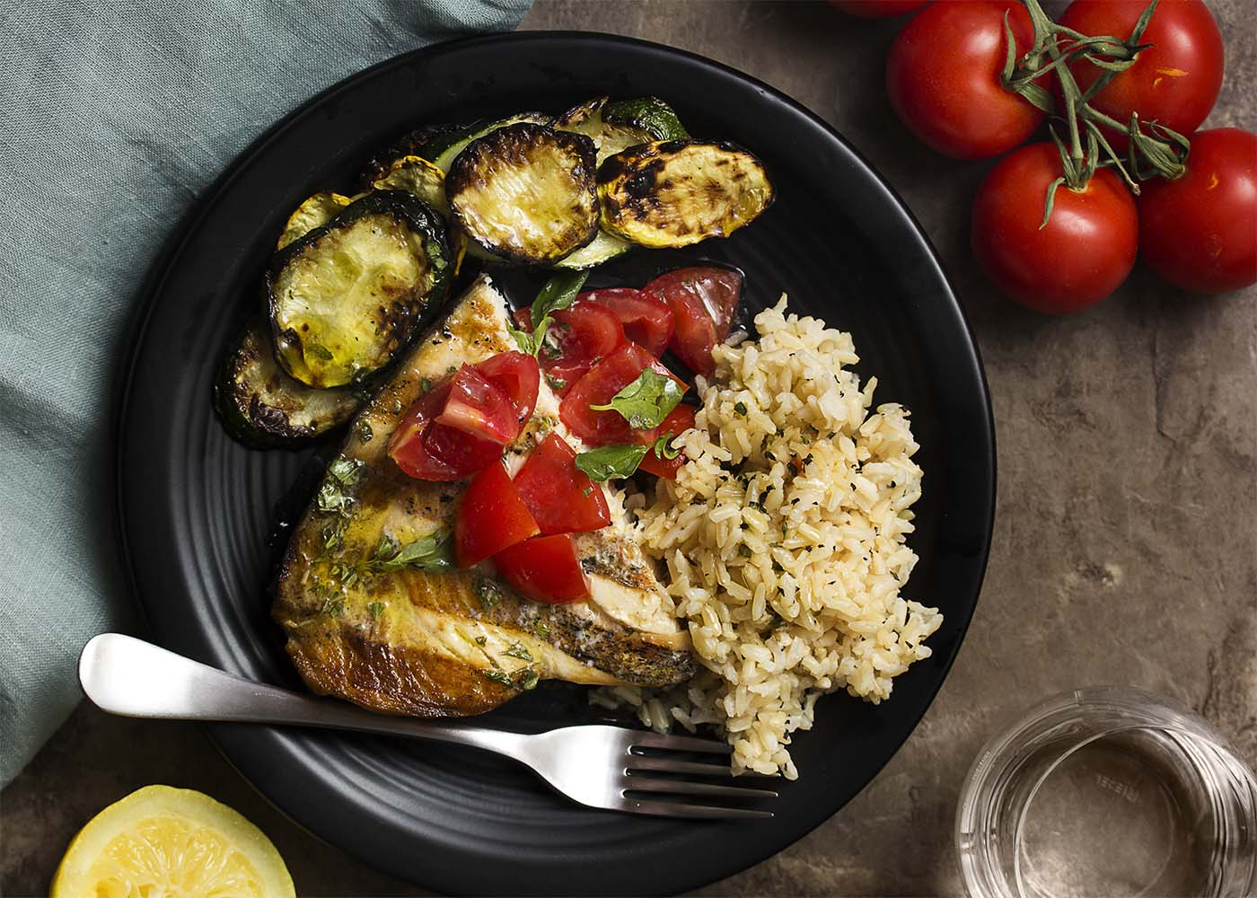 Top view of Sicilian swordfish, grilled summer squash, and rice on a black plate with a fork.