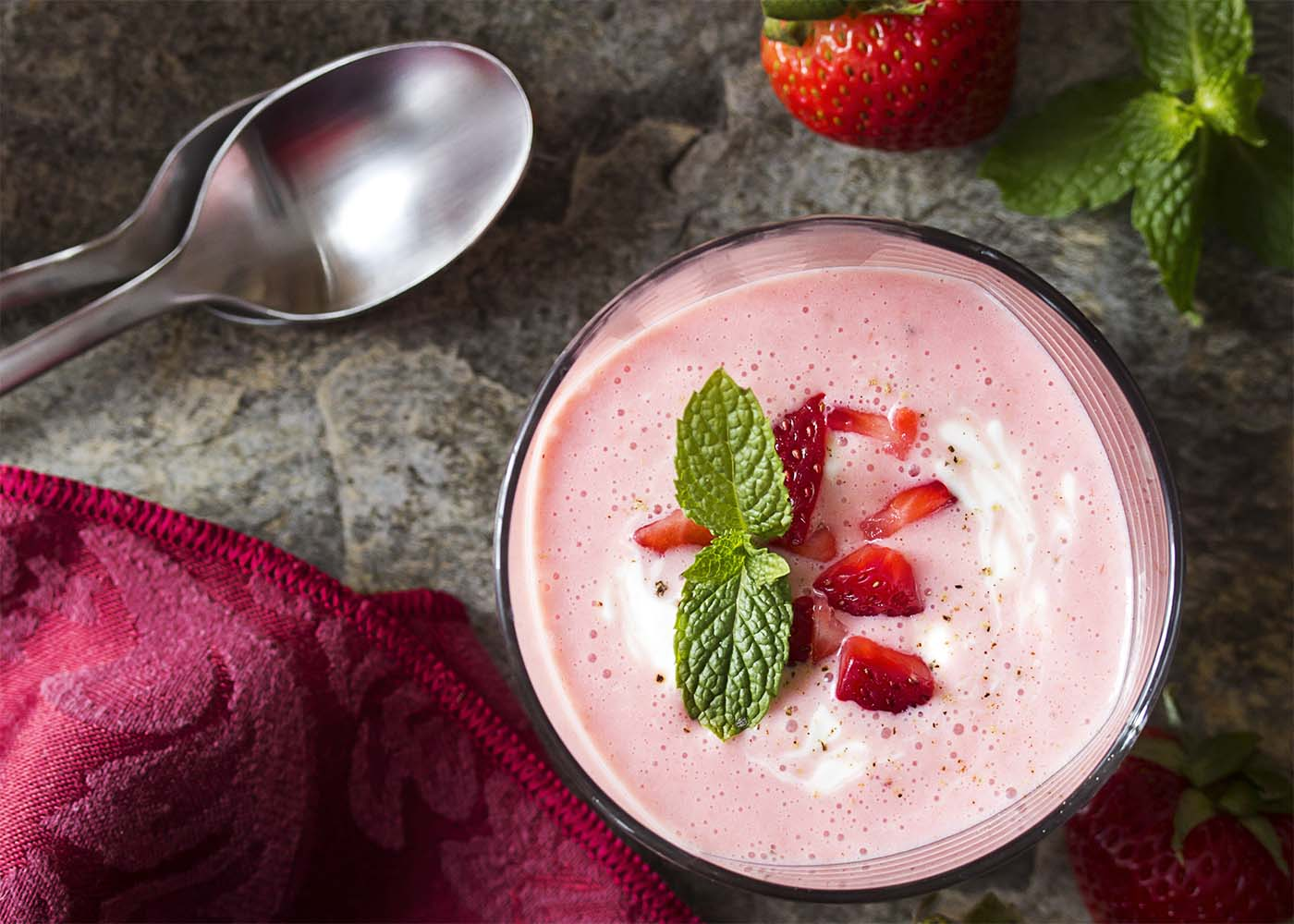 Close up view of a glass cup of strawberry soup with strawberries and spoons scattered about the table.