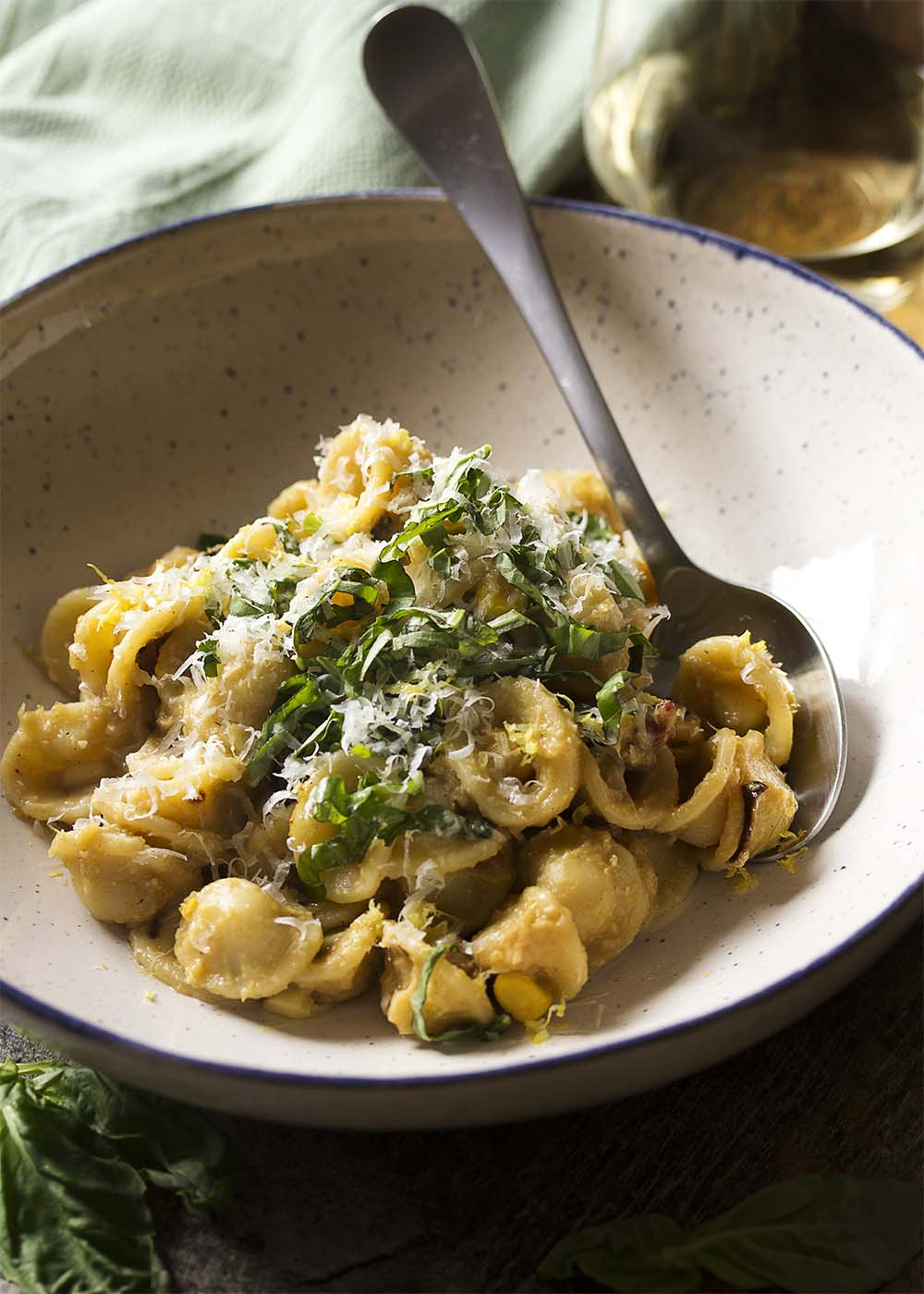 A wide bowl with a spoon of orcchiette with leeks and corn, topped with basil and parmesan cheese.