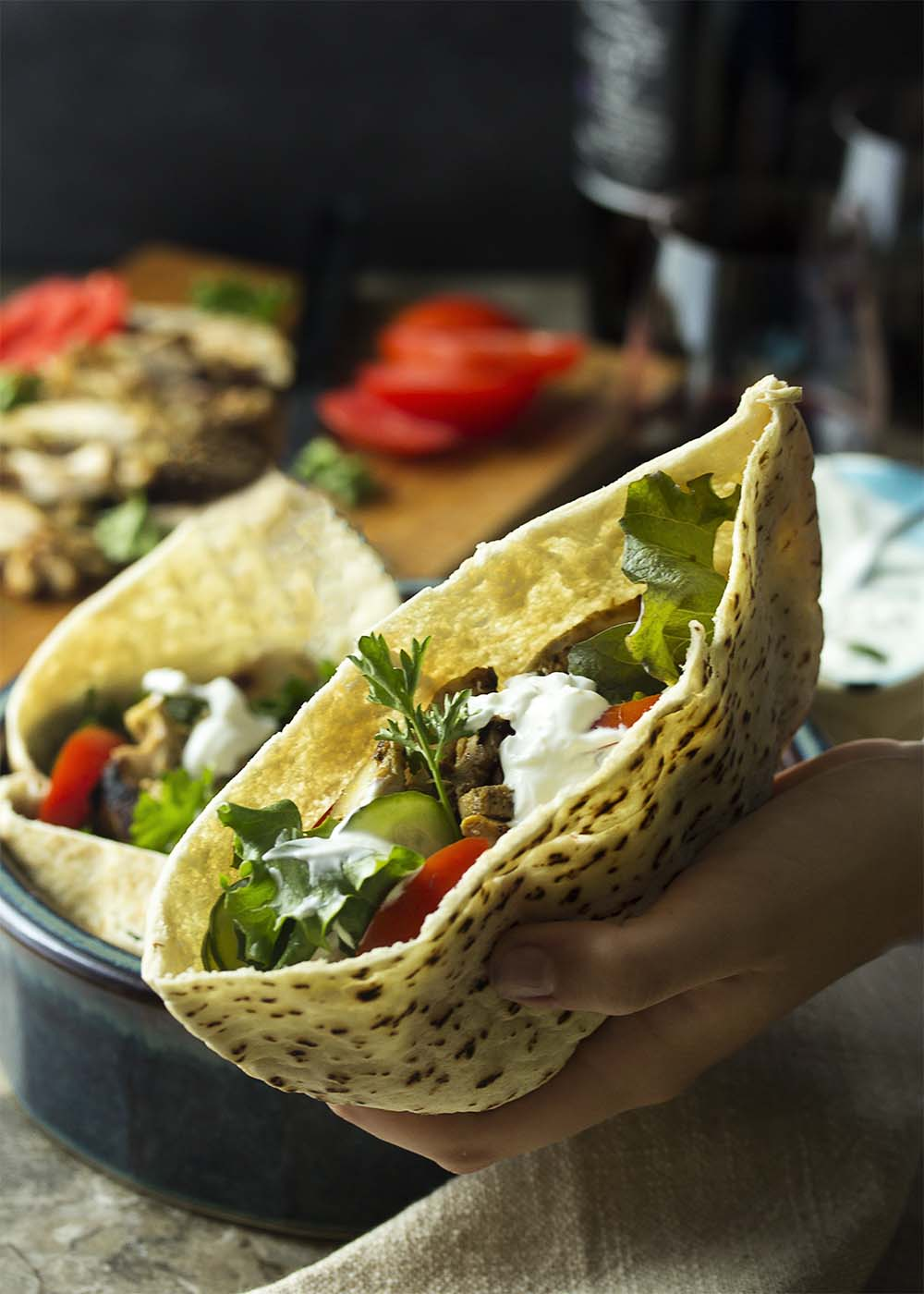 A hand holding out a pita stuffed with chicken shawarma, vegetables, and yogurt sauce.