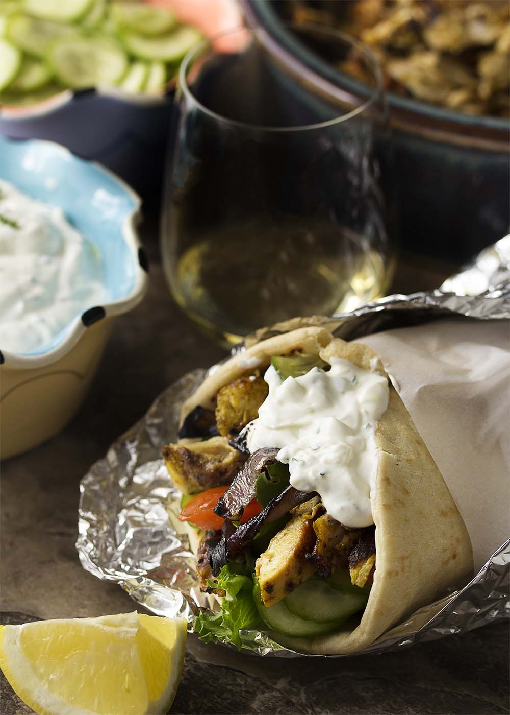 Chicken shawarma pita wrap filled with chicken, veggies, and yogurt sauce and wrapped in foil.