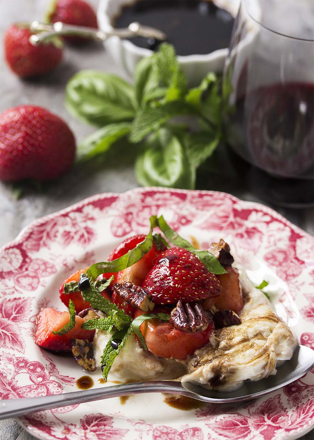 A small salad plate with a strawberry motif piled with strawberries, burrata, herbs, and pecans, and drizzled with balsamic glaze.
