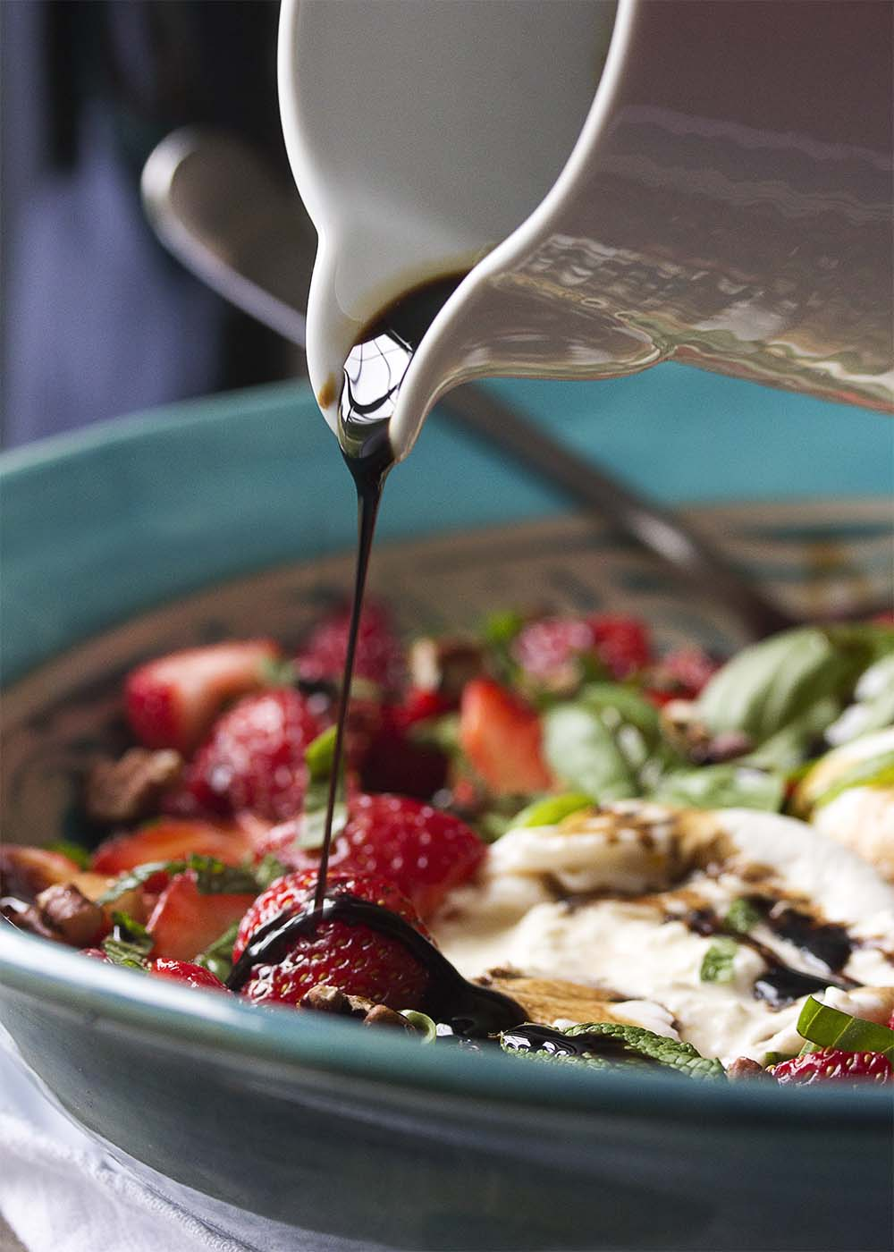 A thin stream of balsamic glaze pouring down from a cup onto a strawberry in the serving bowl of burrata salad.
