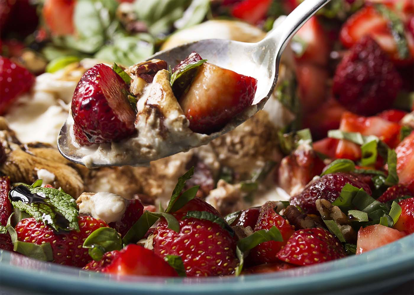 Serving a spoonful of strawberry burrata salad with the serving bowl in the background.