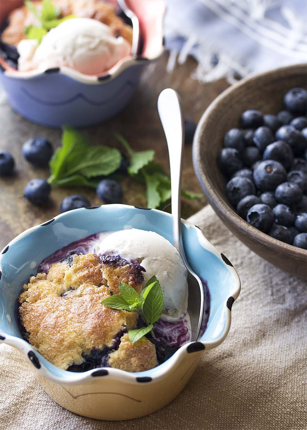 Dessert bowls filled with servings of blueberry skillet cobbler and scoops of vanilla ice cream showing the golden brown biscuit crust and juicy blueberry filling.