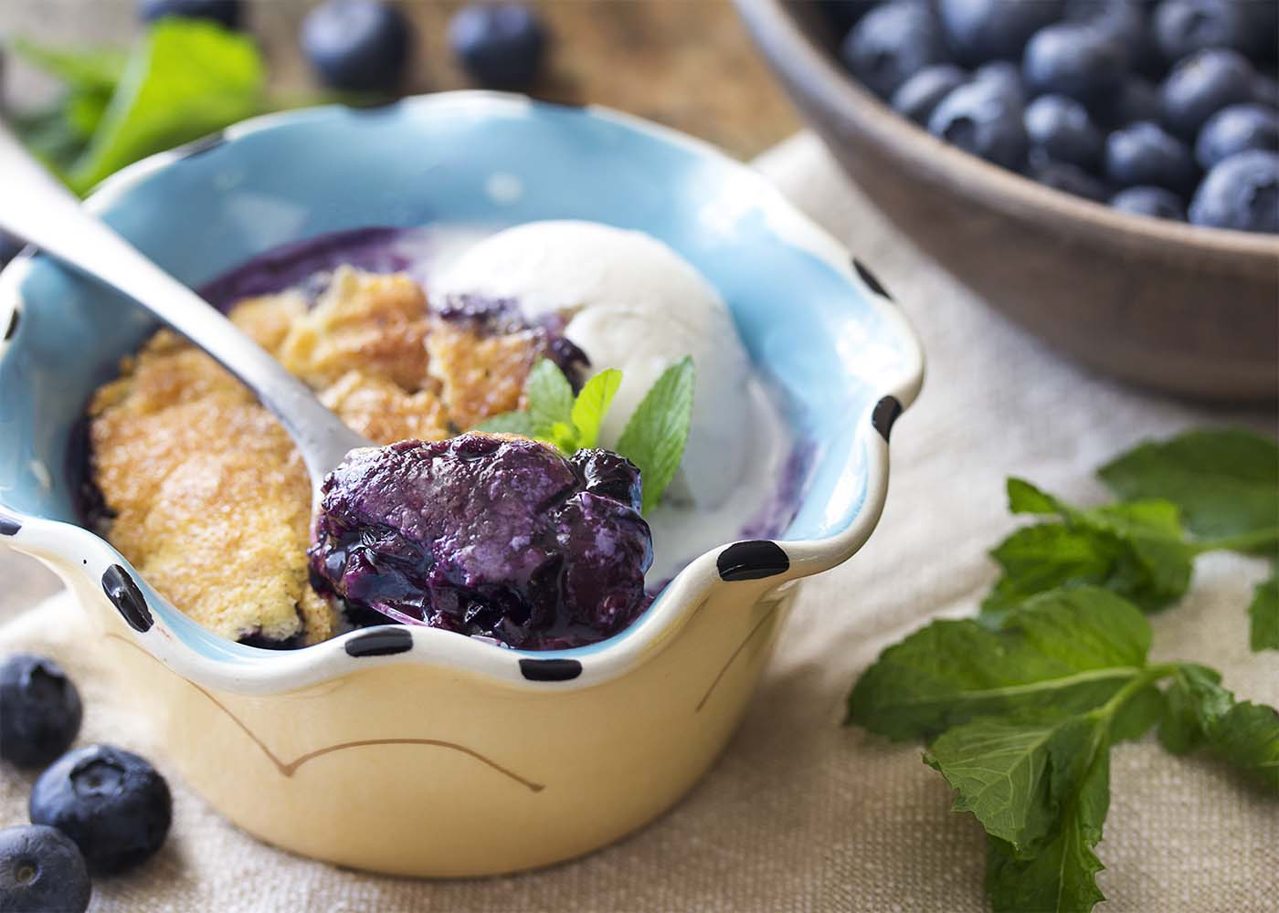 A dessert bowl of cobbler with a spoon scooping out a bite. Blueberries and mint leaves scattered about the table.