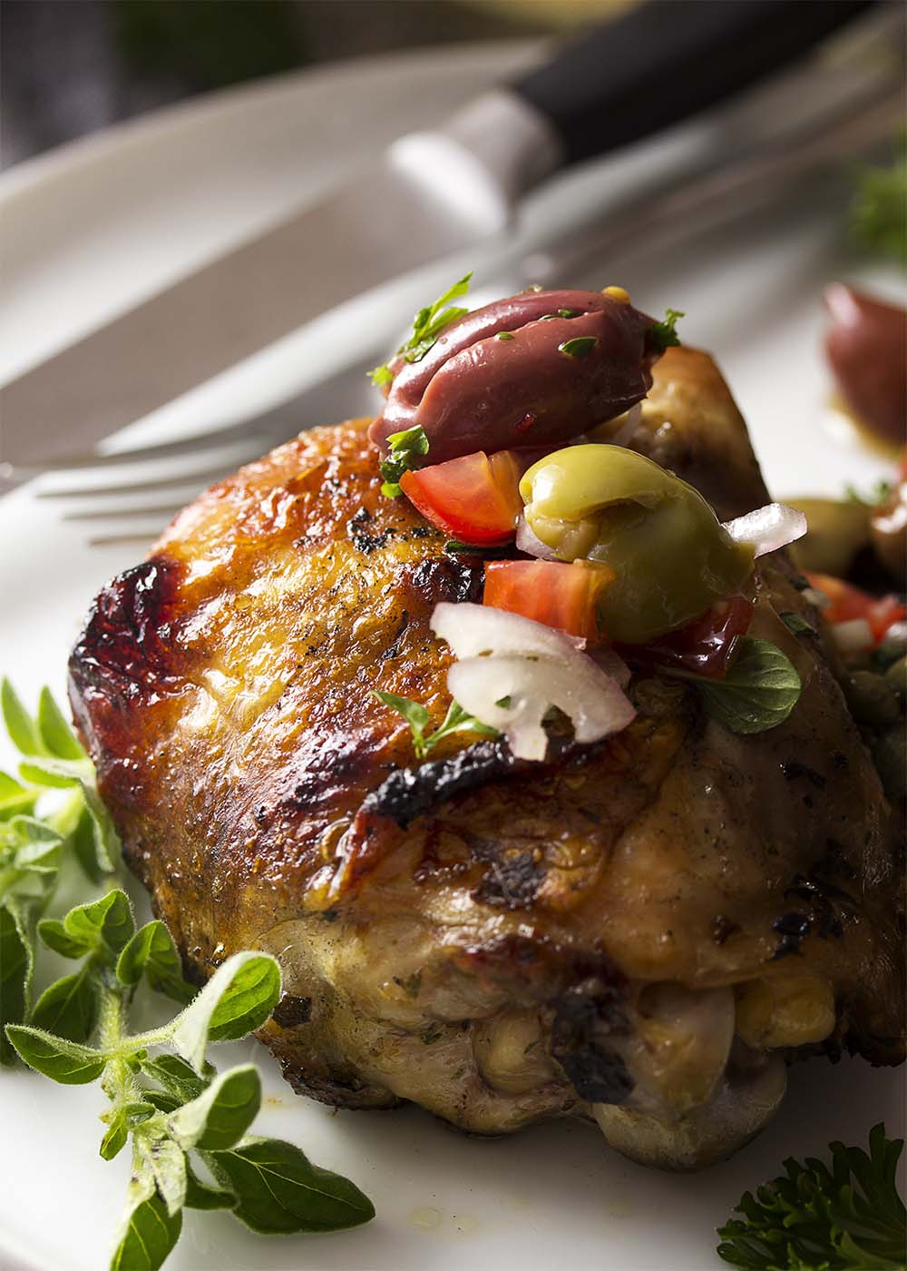 Close up of a grilled Mediterranean chicken thigh with olive tomato salsa spooned over the top and a focus on the crispy skin.