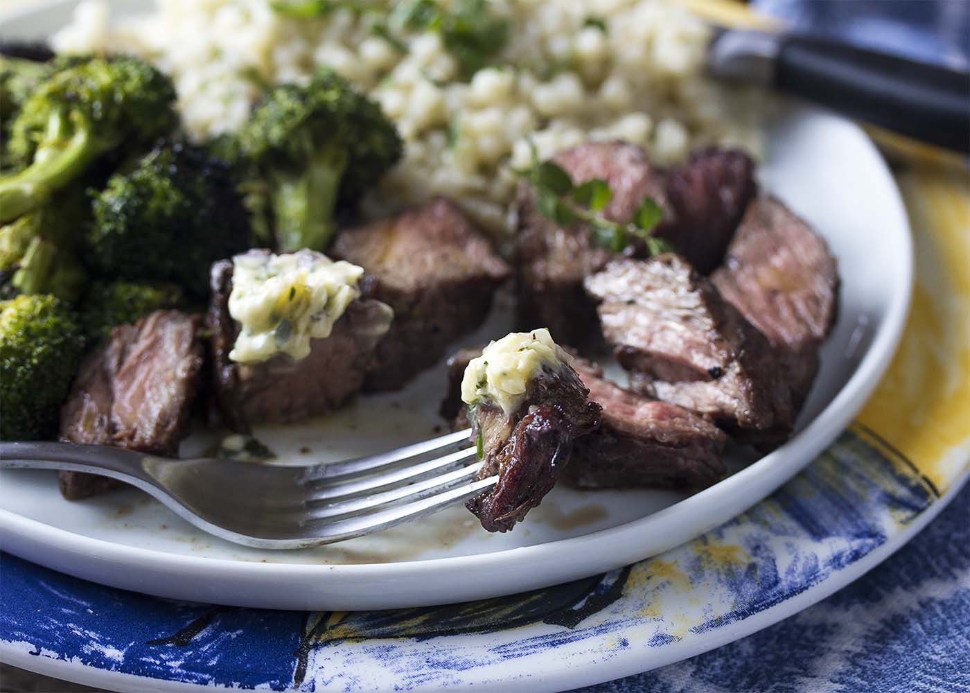 Close up of a slice of grilled sirloin tip on fork topped with the shallot butter and the rest of the plate of steak, broccoli, and couscous in the background.