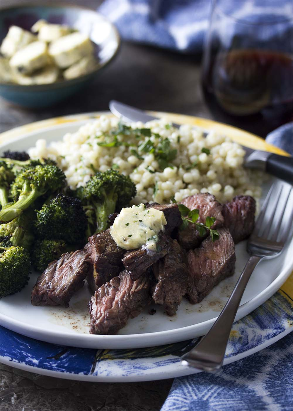 Sliced grilled sirloin tip steaks on a plate topped with shallot butter. Grilled broccoli and Israeli couscous complete the meal.
