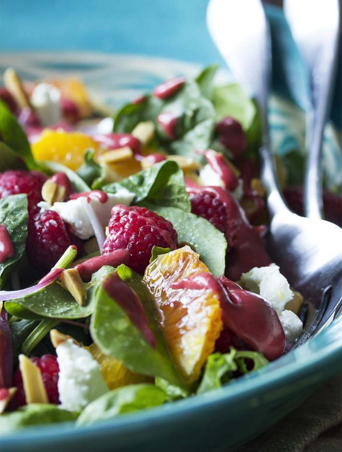 This sweet and tangy summer raspberry salad with mixed greens, oranges, goat cheese, and almonds is an easy and delicious side. Perfect with grilled meats.