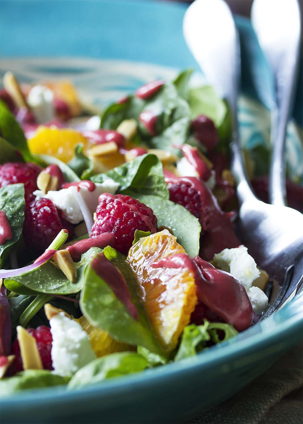 Close up of a serving bowl of raspberry salad with mixed greens, oranges, goat cheese, and almonds.