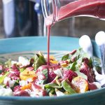 This sweet and tangy summer raspberry salad with mixed greens, oranges, goat cheese, and almonds is an easy and delicious side. Perfect with grilled meats, roasts, or as a side with soup.