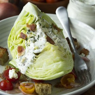 Steakhouse-style classic wedge salad made from iceberg lettuce, topped with buttermilk blue cheese dressing, bacon, and tomatoes is a great dinner side. For date night or for a crowd.