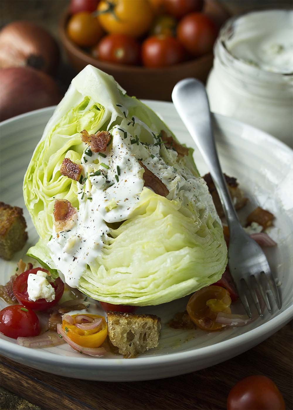A composed plate of classic wedge salad, blue cheese dressing dripping down the sides of the wedge. Bacon, croutons, and tomatoes scattered about the plate.
