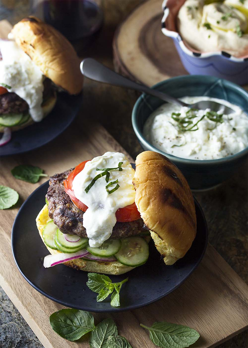 Top view of grilled ground beef Greek burgers layered on a bed of sliced cucumber salad with minty yogurt feta sauce on top.