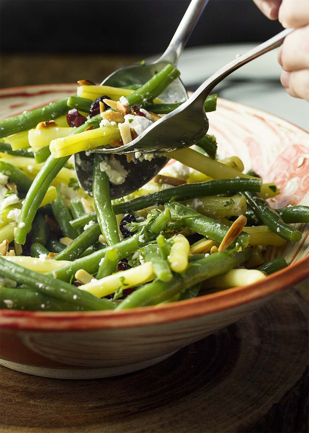 A big serving bowl of green bean salad with fried almonds with salad tongs scooping out a portion.