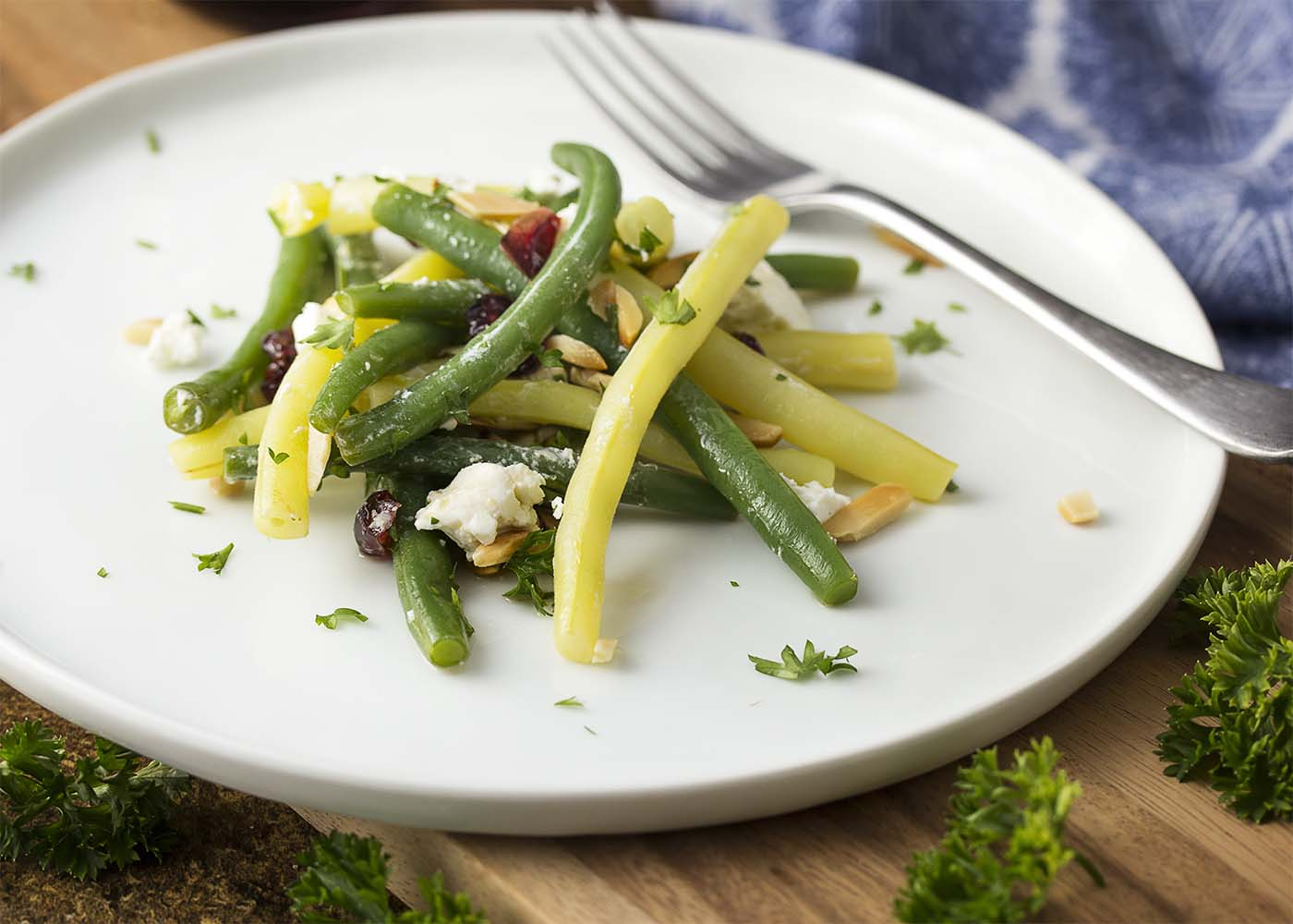 A composed plate of green bean salad showing the almonds, dried cranberries and goat cheese. Chopped parsley scattered about.