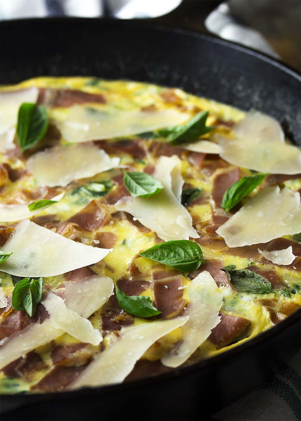 Creamy, fluffy mustard green and leek frittata topped with browned prosciutto, basil leaves and parmesan shavings all in a cast iron pan.