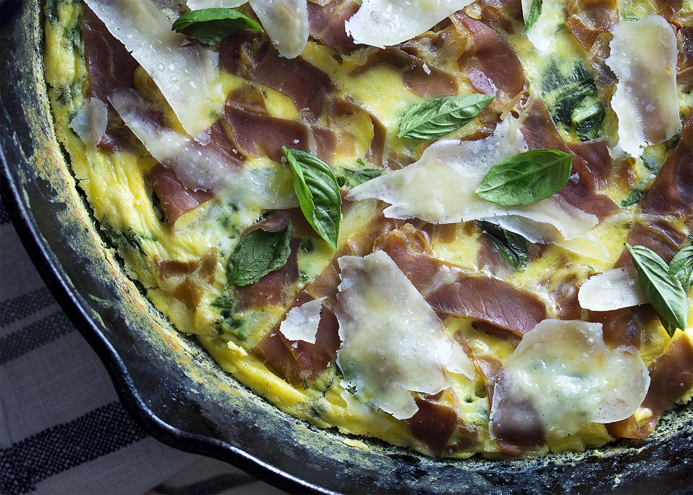 Top view of the finished leek frittata in the cast iron pan. Fluffy eggs are filled with greens and topped with prosciutto, parmesan, and basil leaves.