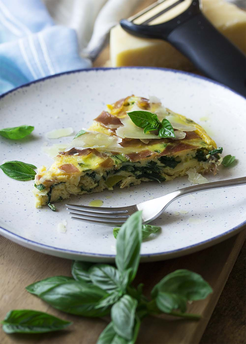 A slice of leek frittata on a plate, showing the leeks and greens in the eggs, with a fork ready to take a piece.