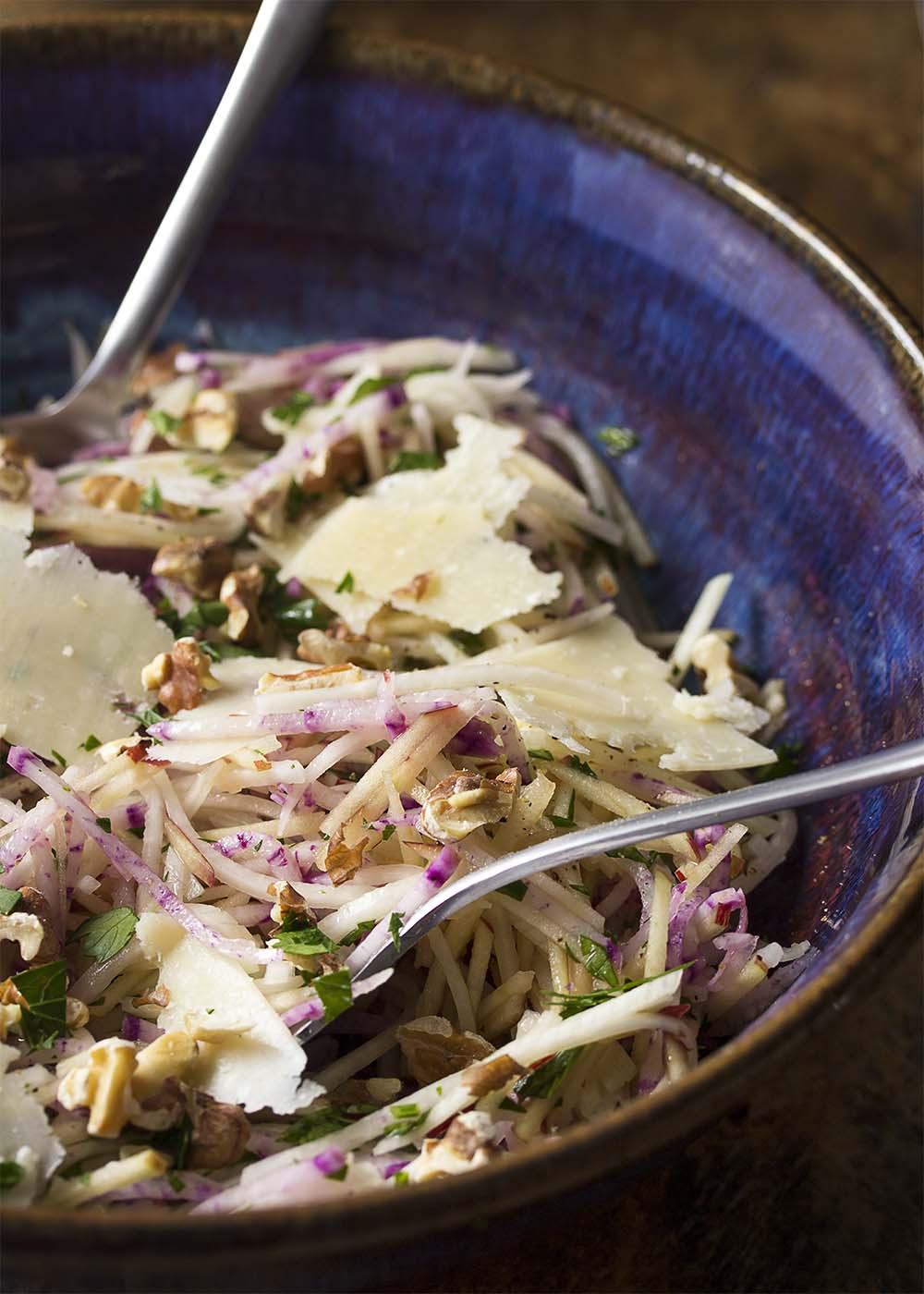 A serving bowl filled with kohlrabi apple and radish slaw, topped with parmesan shavings and walnuts.