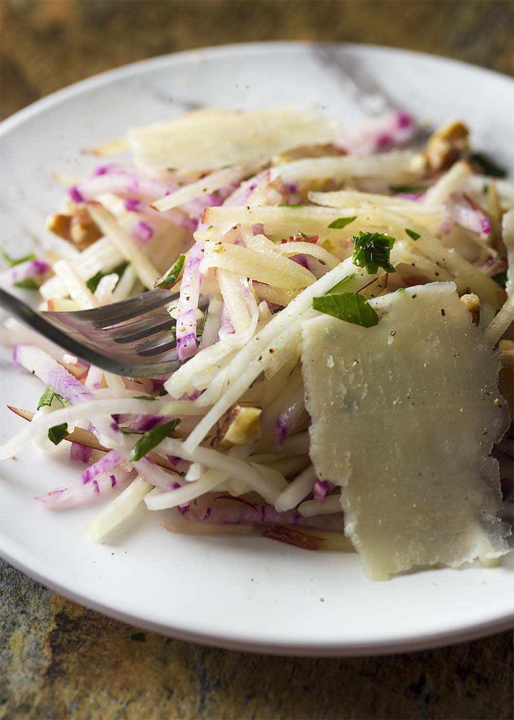 A fork picking up some of kohlrabi slaw from a small dinner plate.