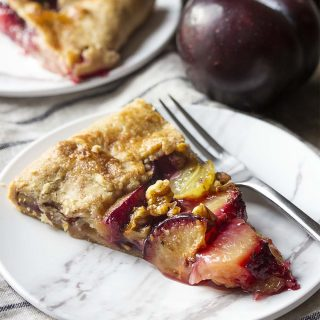 Ripe sliced plums, crisp grapes, and toasted walnuts are wrapped in a simple, flaky pie crust and brushed with honey in this rustic French plum galette tart.