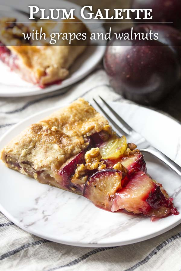 Ripe sliced plums, crisp grapes, and toasted walnuts are wrapped in a simple, flaky pie crust and brushed with honey in this rustic French plum galette tart. | justalittlebitofbacon.com #frenchrecipes #mediterraneanrecipes #pierecipes #tartrecipes #galette #crostata #plums