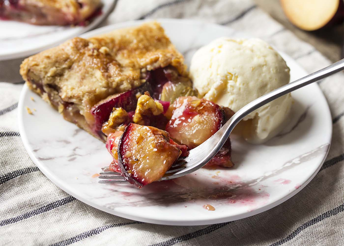 A slice of plum galette on a plate with a scoop of ice cream. A fork cutting a portion off to eat.
