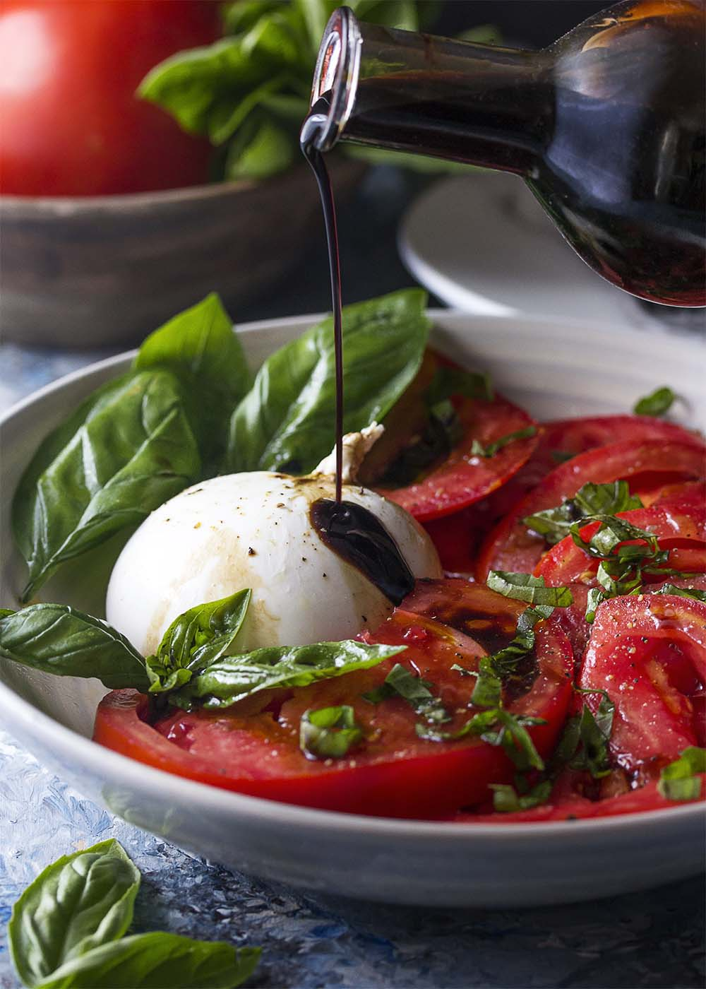 A bowl of sliced tomatoes and burrata topped with basil, olive oil and black pepper with thick balsamic vinegar poured over the top.