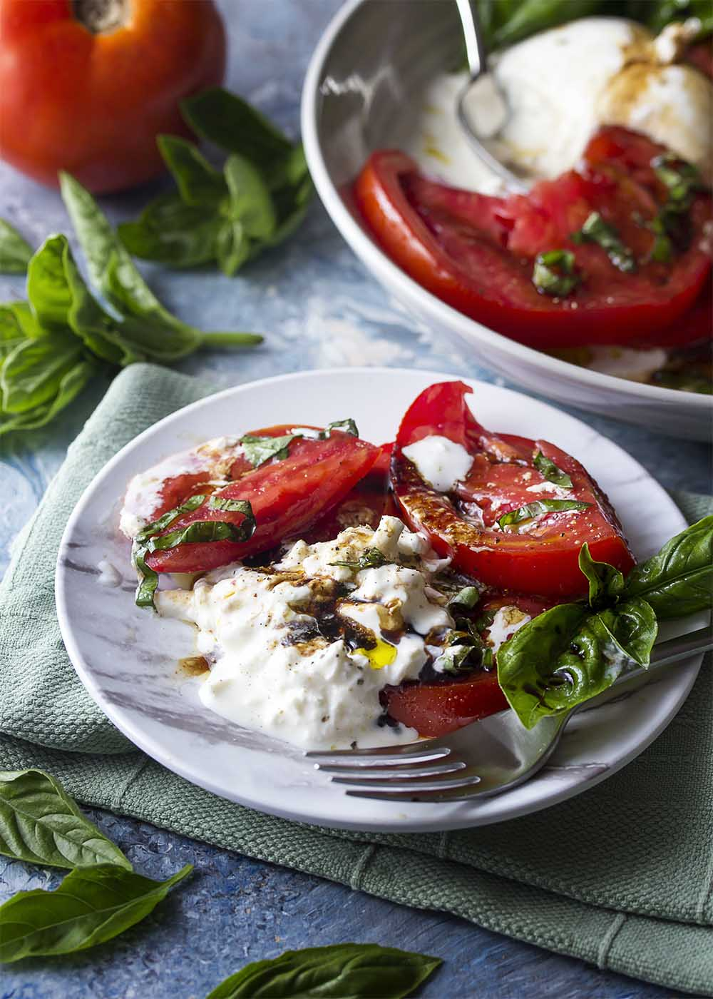 A small plate piled with creamy soft burrata, slices of ripe tomatoes, and fresh picked basil leaves. Extra virgin olive oil and thick balsamic drizzled over the top.