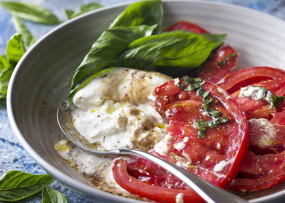 Luscious, creamy burrata broken up in the bowl alongside ripe tomato slices with extra virgin olive oil and thick balsamic mixed into the salad.