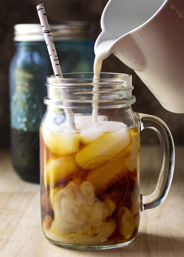 Milk pouring into a glass of cold brew coffee filled with ice.