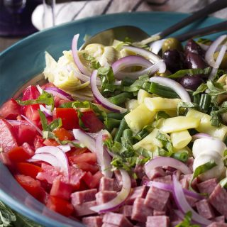 For an easy dinner, serve Italian antipasto salad full of chopped beans and tomatoes, marinated artichoke hearts, salami, fresh mozzarella and all topped with homemade dressing.   justalittlebitofbacon.com #italianrecipe #saladrecipe #antipasto #italian #salad