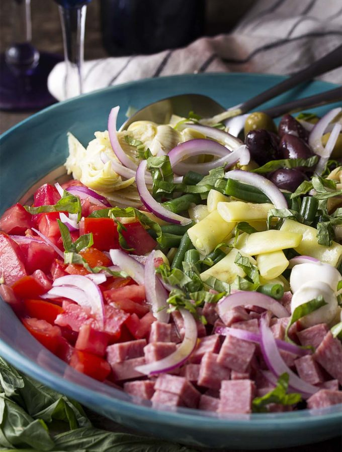 For an easy dinner, serve Italian antipasto salad full of chopped beans and tomatoes, marinated artichoke hearts, salami, fresh mozzarella and all topped with homemade dressing. | justalittlebitofbacon.com #italianrecipe #saladrecipe #antipasto #italian #salad
