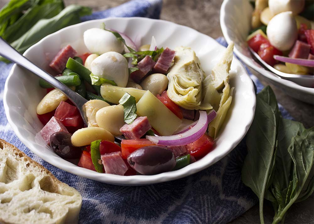 A table with bowls of Italian antipasto salad full of white beans, salami, mozzarella, and tomatoes along with napkins and slices of bread.