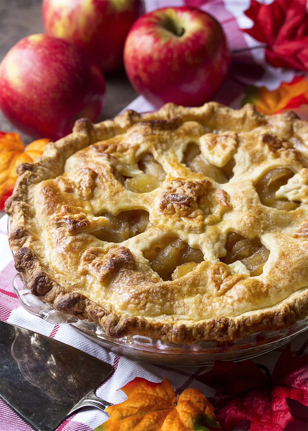 Deep dish apple pie with a golden brown crust and bubbly apple filling surrounded by apples and fall leaves.