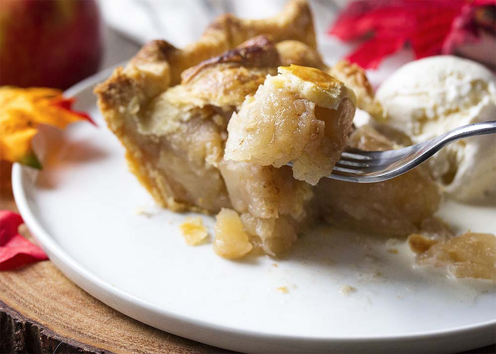 A fork holding up some apple pie in the foreground with a slice of pie and vanilla ice cream in the background.