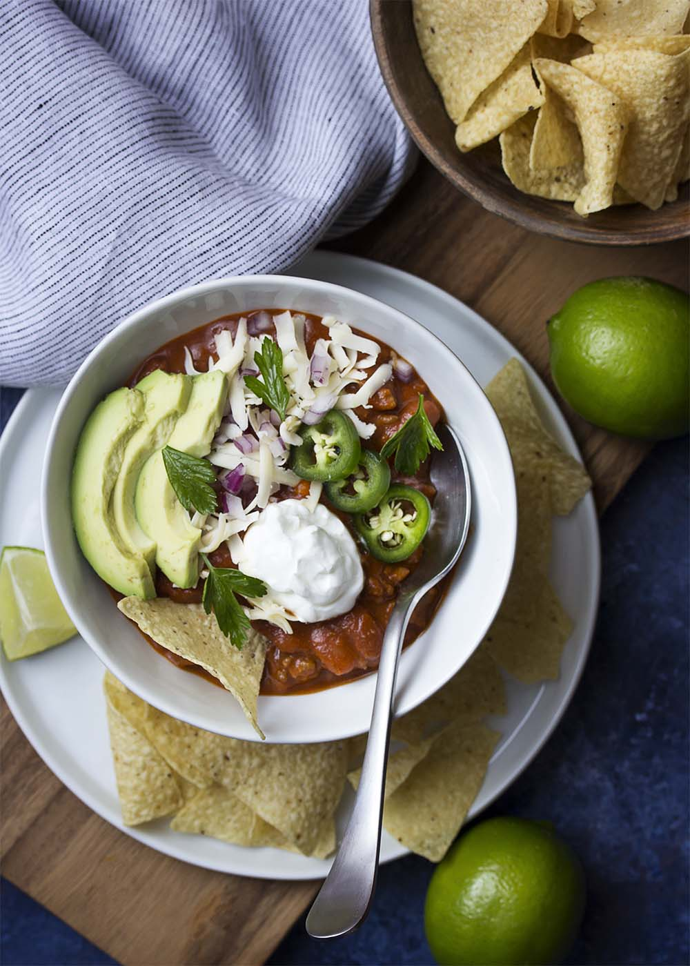 A bowl filled with thick and rich ground beef and bean chili. Topped with avocados, jalapenos , shredded cheese, sour cream, and tortilla chips.
