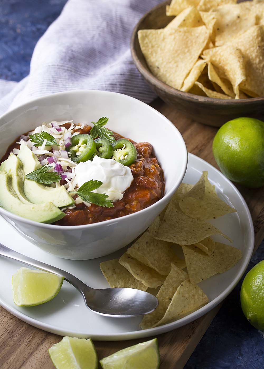 A bowl of loaded ground beef chili set out with tortilla chips and all ready to be enjoyed.