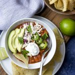 My homemade stovetop ground beef and bean chili is a classic comfort food made even better! It's spiced with dried chiles along a few fresh chiles to balance the flavors and simmered with beer. Great with tortilla chips, avocados, and all the toppings. | justalittlebitofbacon.com #chili #chilirecipe #comfortfood #groundbeef