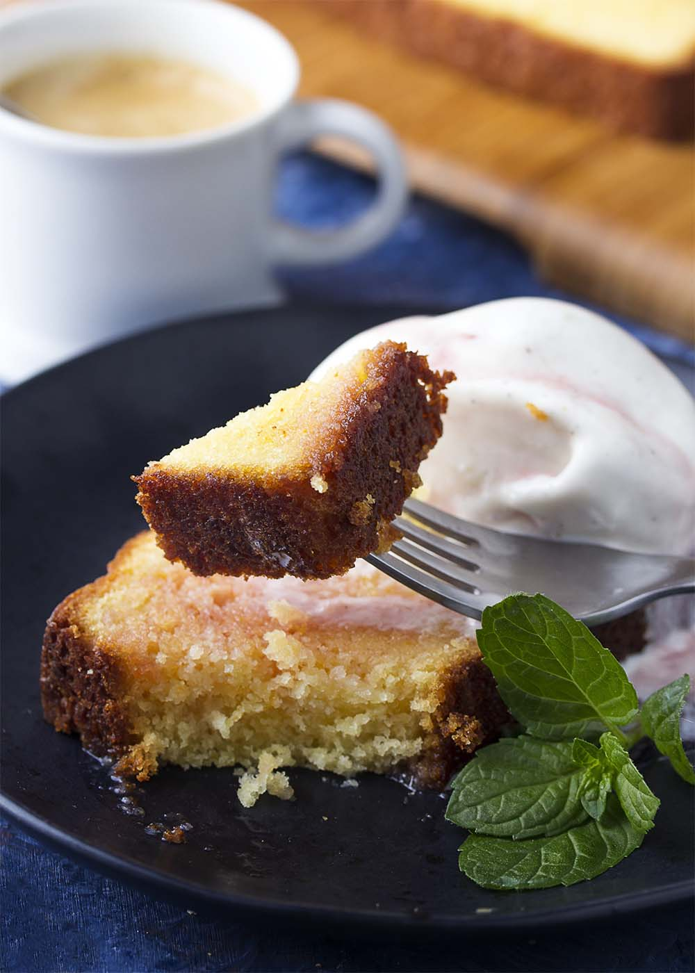 A fork holding up a bite of moist and delicious orange pound cake.