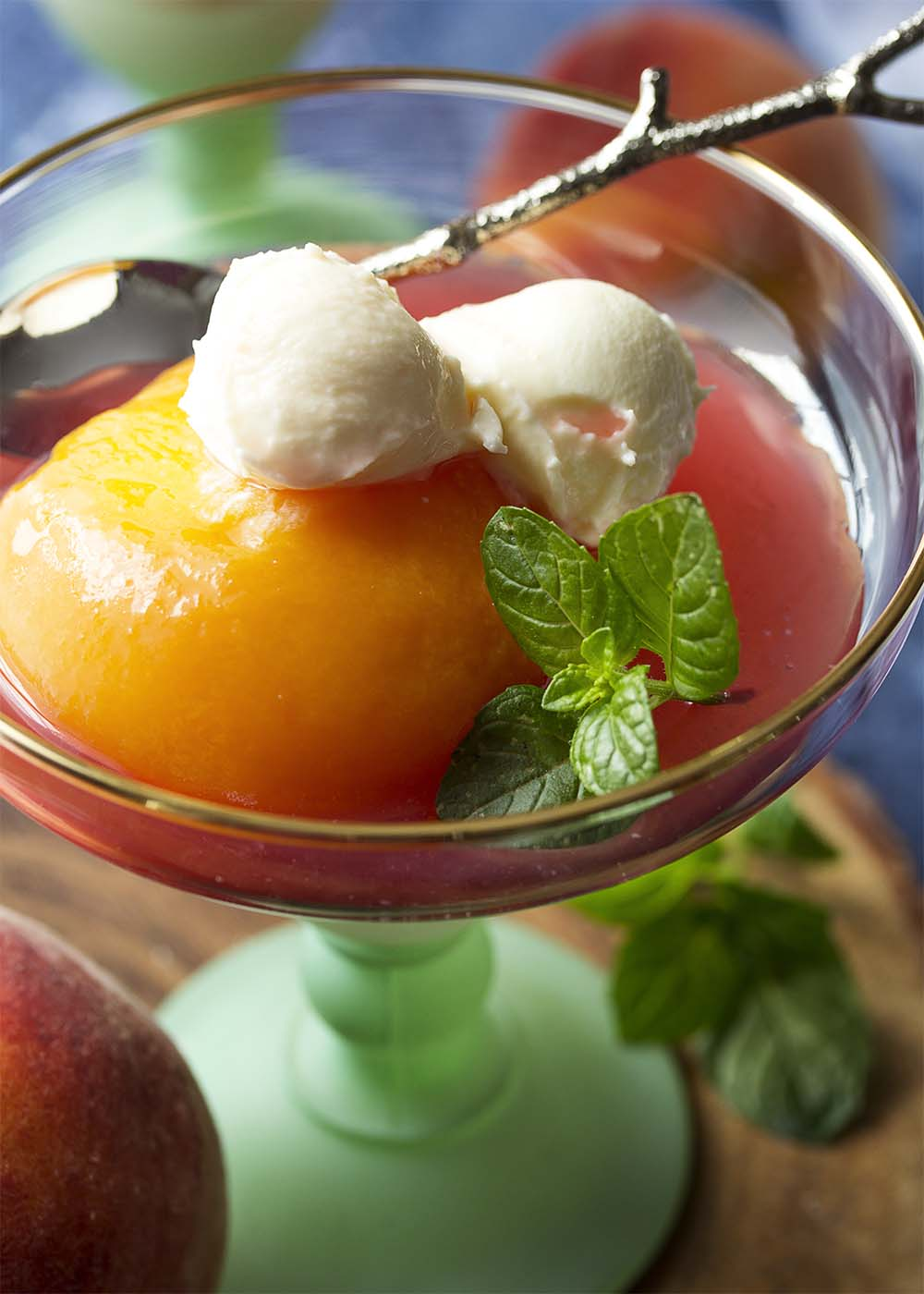 Tender honey poached peach halves are surrounded by a spiced syrup and topped by sweetened mascarpone cheese in a dessert cup.