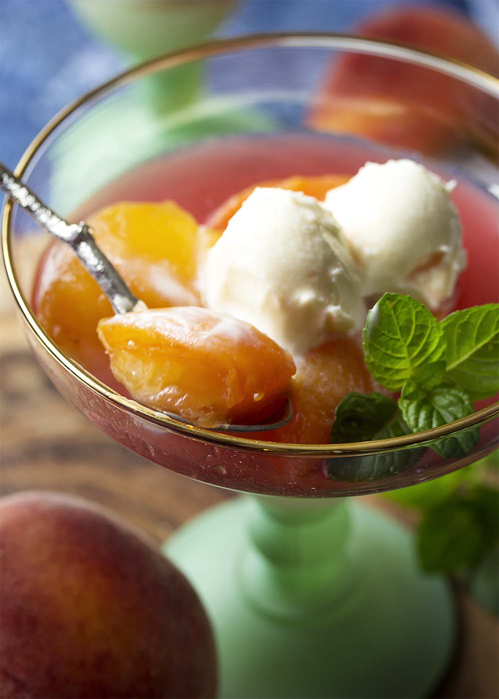A spoon holding up a piece of tender poached peach along with some of the spiced syrup and some mascarpone on top.