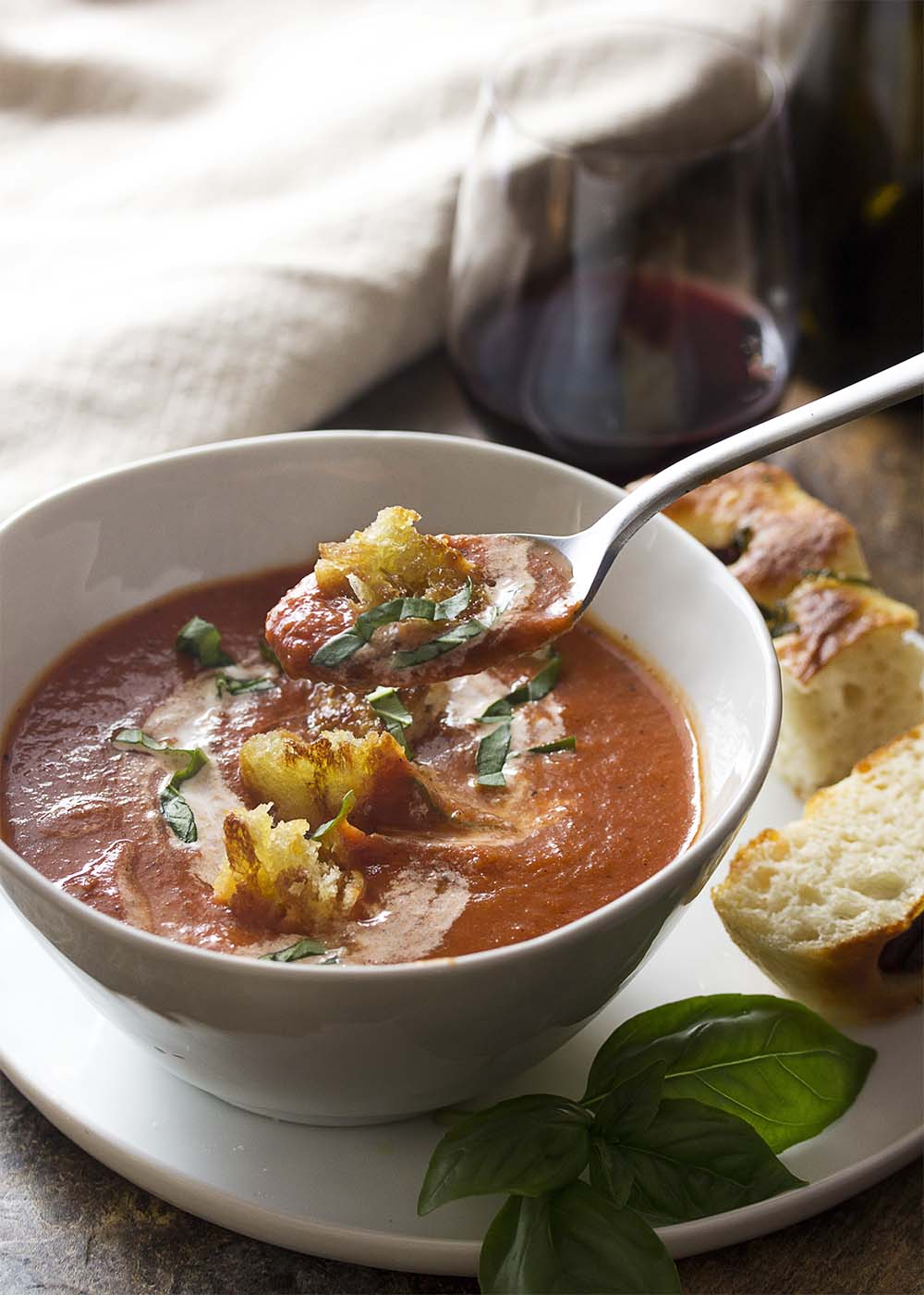 A spoon of tomato soup topped with sliced basil and a fried crouton, focaccia on the plate ready to be dipped in.